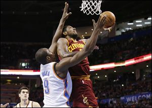 Cleveland Cavaliers guard Kyrie Irving (2) shoots in front of Oklahoma City Thunder forward Serge Ibaka (9).