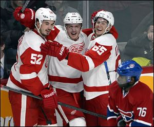 Detroit Red Wings center Gustav Nyquist (14) celebrates his winning goal with defensemen Jonathan Ericsson (52) and Danny DeKeyser (65).