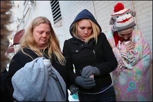 Tracy Bishop, left, her daughter Emily, center, and Elizabeth Mabe pray together during a vigil for firefighters Stephen Machcinski and James Dickman at Magnolia and Huron streets in North Toledo. Ms. Bishop had lived at the site of the fatal fire.