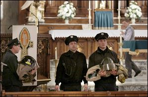 Toledo firefighters carry two fire jackets, boots, and helmets out of the parish during a Catholic Mass at the Historic Church of St. Patrick. The Mass on Wednesday marked the end of the one-month Catholic mourning period for Toledo firefighters James Dickman and Stephen Machcinski.