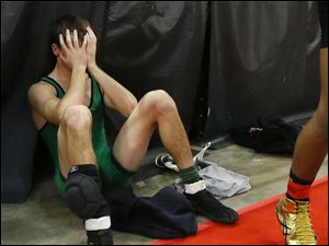 A dejected Dustin Marteney of Delta sits on the floor after losing to Kameron Rayner of Caldwell in their Division III 132 pound match.