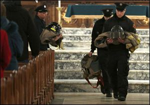 Toledo  firefighters carry two fire jackets, sets of  boots, and helmets during a memorial Mass for two fallen comrades at the Historic Church of St. Patrick.