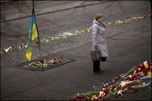A woman stands at a memorial for the people killed in clashes with the police at Kiev's Independence Square.
