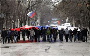 Pro-Russian demonstrators march with a huge Russian flag during a protest in front of a local government building in Simferopol, Crimea, Ukraine today.