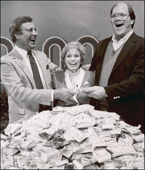 Host Jim Lange, left, congratulates Connie and Steve Rutenbar of Mission Viejo, Calif., after they won $1 million on the TV show