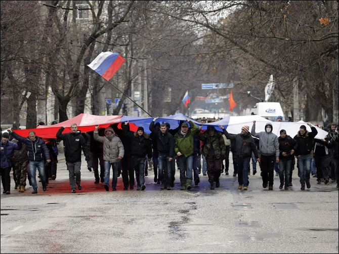 Ukraine Protests PRO-RUSSIA Pro-Russian demonstrators march with a huge Russian flag during a protest in front of a local government building in Simferopol, Crimea, Ukraine today.