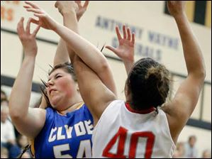Clyde's Jill Miller (54) battles Central Catholic's Demi Russell (40) for a rebound.
