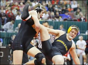 Perrysburg wrestler Rocco Caywood, left, scores a takedown on Dakota Sizemore of Cincinnati Archbishop Moeller in their Division I 182-pound match.