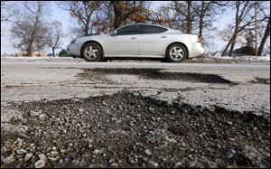 A car passes potholes on Nebraska Avenue near City Park. The city has repaired more than 20,000 potholes so far this season.