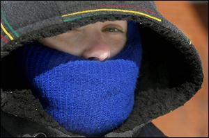 April Sumner, originally from Florida, bundles-up so much that only her nose and eyes are visible under her coat and hat during record cold temperatures on Feb. 12.