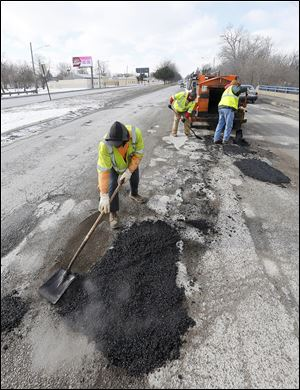 City employees, from left, Bernie Hamilton, Sammie Coleman, Jr., and Jeff Green fill potholes while traffic flies past them Wednesday on Anthony Wayne Trail. Rude, reckless drivers can be a frequent problem for rolling work zones.