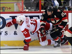 Ottawa Senators' Chris Neil (25) checks Detroit Red Wings' Daniel Alfredsson (11) during second period.