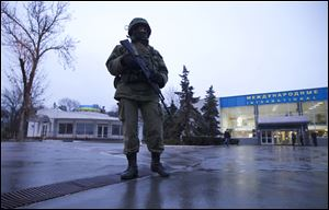 An unidentified armed man patrols a square in front of the airport in Simferopol, Ukraine, today.  Dozens of armed men in military uniforms without markings occupied the airport in the capital of Ukraine's strategic Crimea region.