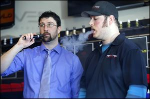 Manager Jordan Salkil, left, and sales clerk Austin Zaborowski 'vape' an ecigarette behind the counter at the Revolver Electronic Cigarettes & Vapor Lounge.