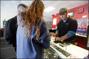 Austin Zaborowski, right, a sales clerk at Revolver Electronic Cigarettes & Vapor Lounge, helps customers buy an ecigarette.
