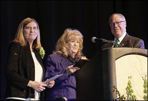Sandra Drabik, left, and her husband, Mayor D. Michael Collins, present former Toledo Councilman Betty Shultz with