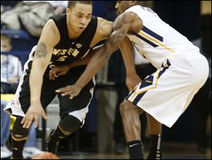 WMU's David Brown (5) is defended by UT's Rian Pearson (5).