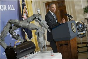 Beside a set of robotic arms, President Obama spoke about manufacturing innovation institutes last week at the White House.