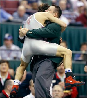 Central Catholic's Nate Hagan leaps into the arms of coach Antonio Guerra after defeating Brent Moore of St. Paris Graham. A skin issue kept him out of last year's tournament.