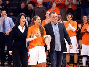 Jillian Halfhill, center, is escorted onto the court with her mother Renee Halfhill, left, and her stepfather Bernie Carpenter on Senior Day.