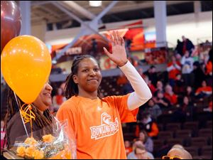 Alexis Rogers waves to the crowd on Senior Day. She is flanked by her mother Youlanda Rogers, left, and her cousin Zion Rogers.