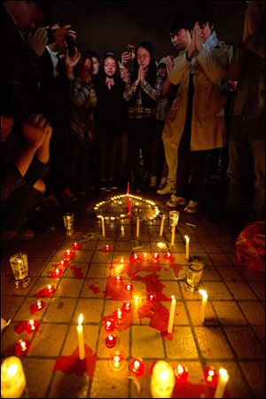 People light up candles and pray for the victims on a square outside the Kunming Railway Station where more than 10 assailants slashed scores of people with knives the night before in Kunming, in western China's Yunnan province, Sunday.