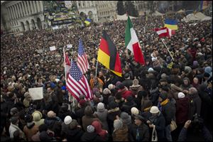 Protesters holding U.S., German and Italian flags arrive at Independence Square during a rally Sunday in Kiev.