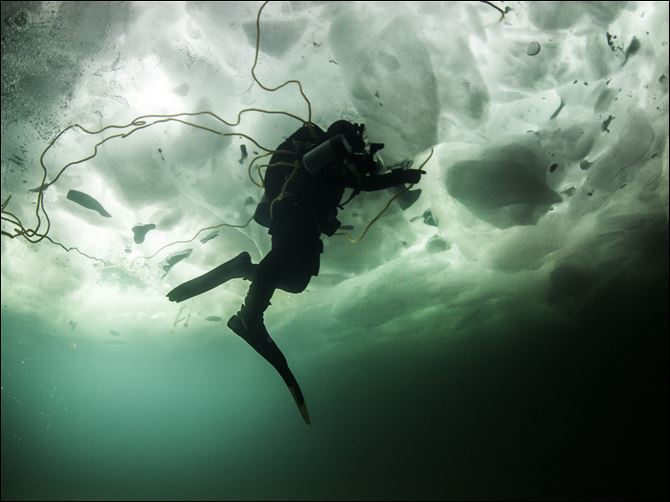 MAG Ice2p Rich Synowiec of Monroe swims beneath 20 inches of Lake Erie ice during a dive in Colchester, Ont.