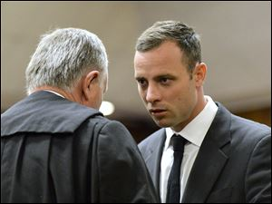Oscar Pistorius, right, speaks with his lawyer Barry Roux as the start of his trial is delayed at the high court in Pretoria, South Africa, today, March 3, 2014. Pistorius is charged with murder with premeditation in the 2013 shooting death of girlfriend Reeva Steenkamp.