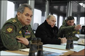 Russian President Vladimir Putin, center, Defense Minister Sergei Shoigu, left, and Chief of Staff Training Directorate Gen. Ivan Buvaltsev, watch an exercise near St. Petersburg, Russia. Officials there say they are protecting Russians in Crimea.