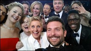 This image released by Ellen DeGeneres shows actors front row from left, Jennifer Lawrence, Meryl Streep, DeGeneres, Bradley Cooper, Peter Nyong'o, Jr., and, second row, from left, Channing Tatum, Julia Roberts, Kevin Spacey, Brad Pitt, Lupita Nyong'o and Angelina Jolie as they pose for a selfie during the Oscars. The popular posting crashed Twitter for a few minutes on Sunday.