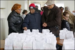 Antoinette Goodloe, Jonathan Goodloe, and Neail Goodloe III, right, shop for paczki Sunday during the 24th annual 'Paczkowy Fest' in the historic Polish Village in Toledo.