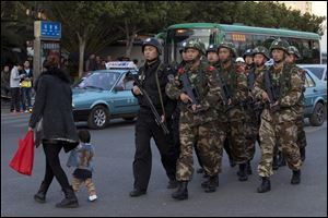 Armed policemen and paramilitary policemen patrol a street near the Kunming Railway Station today, where more than 10 assailants slashed scores of people with knives Saturday evening, in Kunming, in southwestern China's Yunnan province.