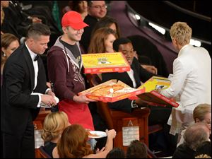 Edgar Martirosyan, center with red hat, delivers pizza to Brad Pitt, left, and Ellen DeGeneres, right, during the Oscars show on Sunday.