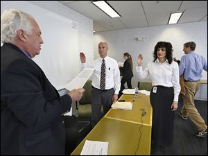 Ron Rothenbuhler, left, chairman of the Lucas County Board of Elections, swears in Dan DeAngelis as deputy director of the board and Gina Kaczala as the new director as outgoing director Meghan Gallagher and board member Jon Stainbrook leave the room.