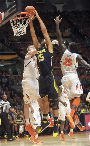 Michigan forward Jon Horford (15) goes up for a dunk between Illinois forward Jon Ekey (33) and guard Kendrick Nunn (25).