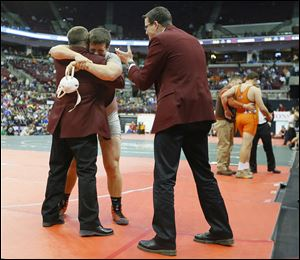 Genoa junior Jay Nino hugs assistant coach Dave Wlodarz as head coach Bob Bergman applauds after Nino beat New Paris National Trail's Ben Sullivan to win the Division III 220-pound state title — his 65th victory, an Ohio record for a season.