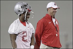 Ohio State coach Urban Meyer, right, laughs with cornerback Armani Reeves during the Buckeyes' first practice of spring.