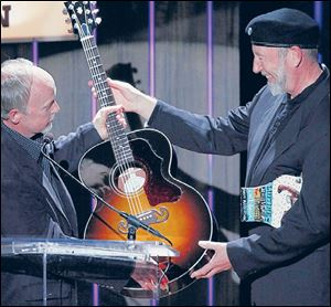 Richard Thompson, right, receives a Gibson guitar from Dave Berryman, president of the guitar company, after being awarded the Lifetime achievement Songwriting Award in Nashville in 2012.