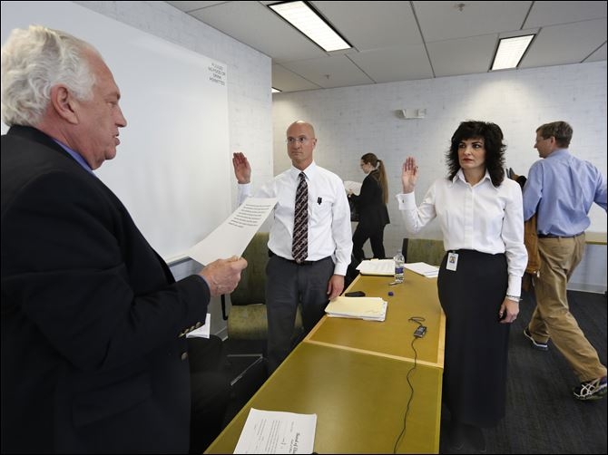 CTY elections04p sworn in  Lucas County Board of Elections chairman Ron Rothenbuhler, left, swears in Dan DeAngleis as deputy director of the board, and Gina Kaczala as the new director, durin