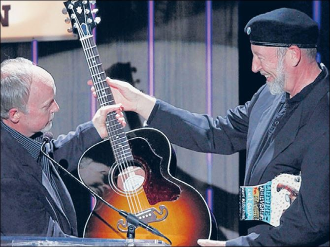 Richard Thompson, right, receives a Gibson g Richard Thompson, right, receives a Gibson guitar from Dave Berryman, president of the guitar company, after being awarded the Lifetime achievement Songwriting Award in Nashville in 2012.
