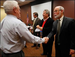 Dr. Larry Cook, left, shakes hands with John Kornbluh, Project Architect at Burgess & Niple, right.