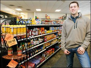 Zac Oswald, of Berkey, among the grocery items the store sells, including locally produces mustard, sloppy joe sauce, and barbecue sauce.