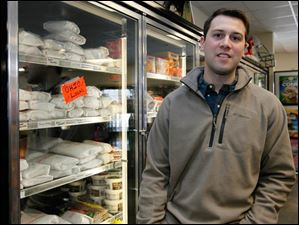 Zac Oswald, of Berkey, next to freezer with locally processed meats, including pork chops, steaks, and casing hot dogs.