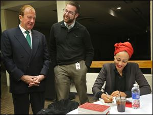 Author Zadie Smith jokes with John Szuch, left, and Steve Szuch as she signs books at the 2014 Authors! Authors! series at Stranahan Theater in South Toledo.