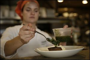 Rebecca Wilcomb, chef de cuisine at Herbsaint Restaurant in New Orleans, plates braised short rib with potato rosti and horseradish cream.