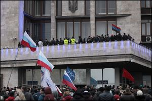Demonstrators hold Russian flags during a rally in front of the regional administrative building after storming it in Donetsk, Ukraine. The United States and its European allies have agreed to send more money to Ukraine.