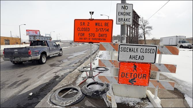 Signs warn of the Anthony Wayne Bridge's closure for ex­ten­sive re­pairs and ren­o­va­tion, a project that will begin March 17 and continue for 19 months.