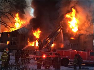 Firefighters battle a four-alarm fire at a three-story apartment complex Wednesday morning on Detroit's west side.