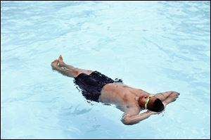 A swimmer floats on his back at Wilson Pool in Toledo in this 2013 photo. Wilson, along with five other pools and a splash pad, could be open again if funding sources are found.
